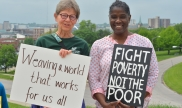 """People hold signs saying """"Weaving a world that works for us all"""" and """"Fight poverty not the poor"""""""