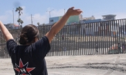 Woman waving in front of U.S. Mexico border wall