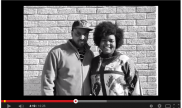 Video screenshot of man and woman standing in front of brick wall