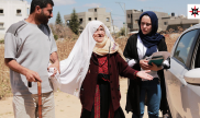Two aide workers helping an elderly Palestinian woman