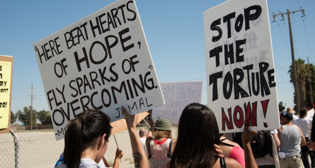 """Protestors carrying signs reading """"Here beat hearts of hope, fly sparks of overcoming"""" and """"Stop the torture now"""" in support of Corcoran Prison hunger strikers, California, 2013."""