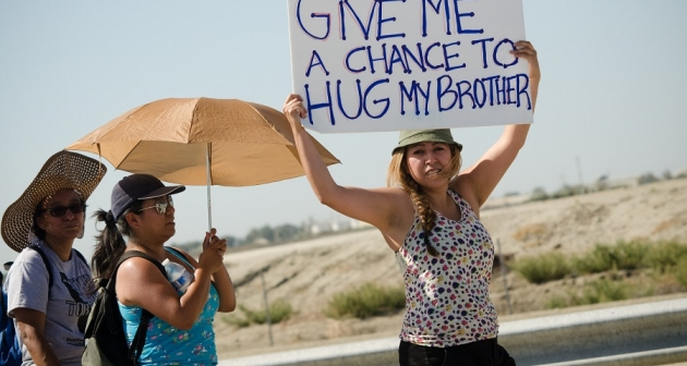 "Woman with a sign reading ""Give me a chance to hug my brother"" at a rally in support of hunger strikers at Corcoran State Prison, California, 2013."