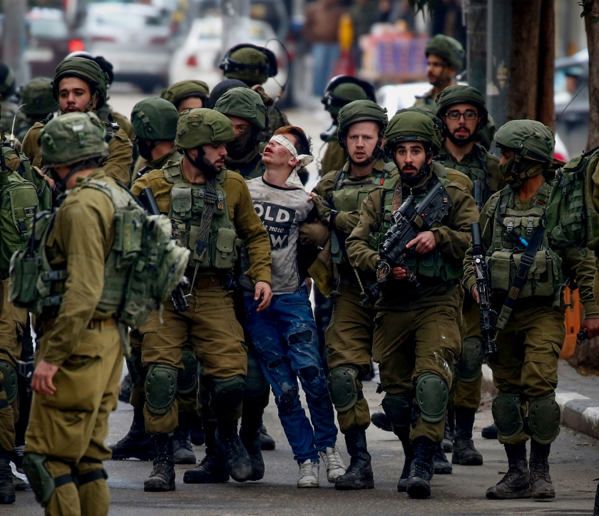 Blindfolded youth surrounded and held by Israeli soldiers
