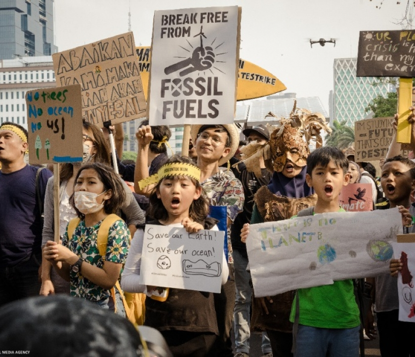 Children holding protest signs at a climate strike in Indonesia