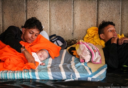 Migrants with children laying on a makeshift bed