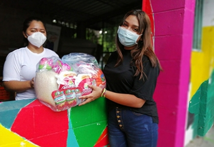 Two people wearing masks handing off pandemic relief supplies