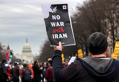 """Protester with a sign that says """"no war with Iran"""""""