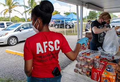 A person in an AFSC t-shirt and another person in a mask giving out pandemic relief supplies