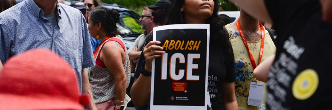 Young woman holds abolish ICE sign at Lights of Liberty protest in Philadelphia