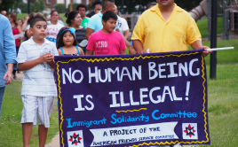 """Man and children holding """"no one is illegal"""" banner"""