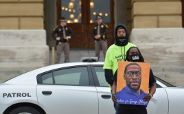 Protestor holding portrait of Georg Floyd as police stand in background