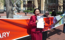 Oakland Mayor Jean Quan stands in front of banner