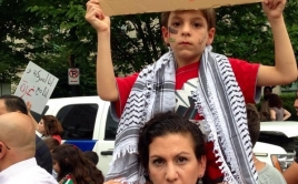 """Zeina with her son Mejd who is holding a sign that says """"Save the children of Gaza"""""""