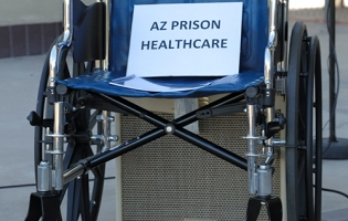 empty wheelchair holds a copy of new AFSC report on prison healthcare in Arizona