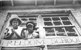 "two girls in school building window with sign that says ""freedom school"""