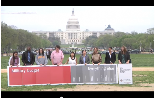Youth with banner showing federal spending in front of the White House