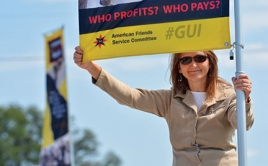 woman holds up sign asking who profits and who pays