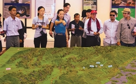 group gathered around a model of the region