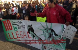 No Human Being is Illegal banner held up by dozens at rally in Tacoma, Wash.