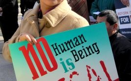 """Yazmin holds a sign that says """"No human being is illegal"""""""