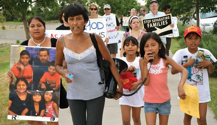 group marches holding signs about ending immigration policies that harm families