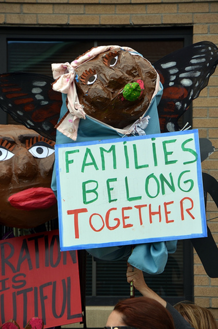 Puppet holding sign that says families belong together