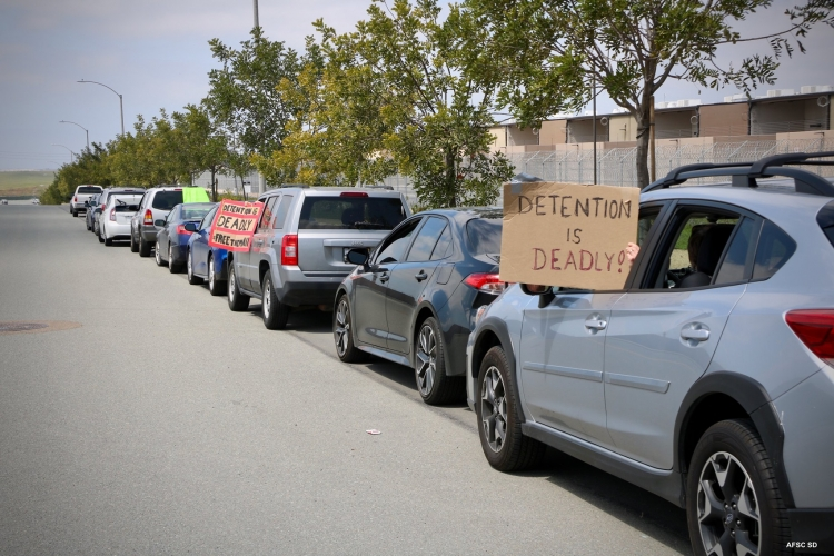 Line of cars with signs saying 'Detention Is Deadly'