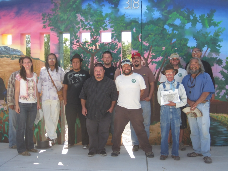 Farmers stand in front of mural