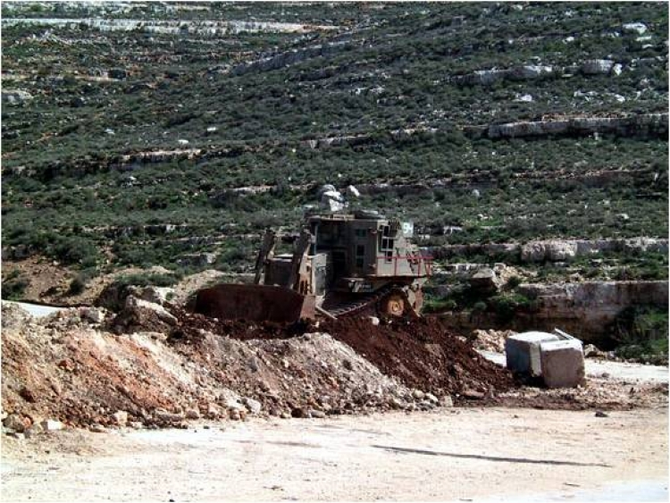 A militarized Caterpillar D9 bulldozer creates a roadblock in the West Bank