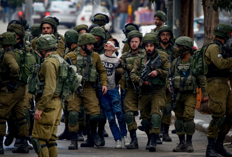 Israeli military detaining a young man