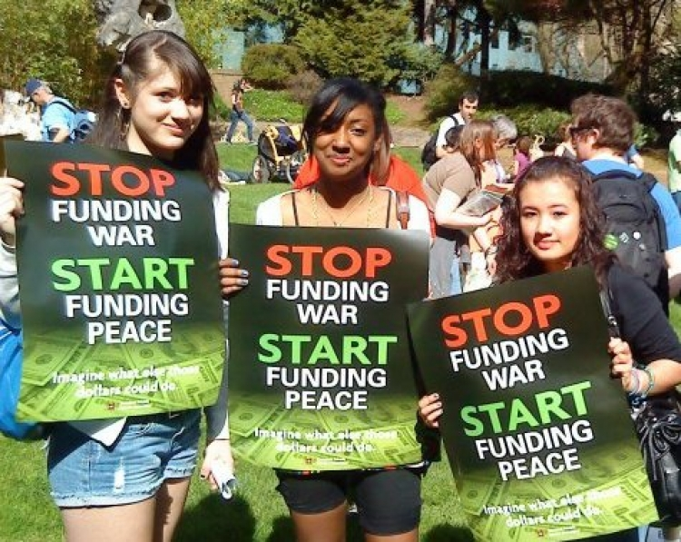 3 young women holding stop funding war signs