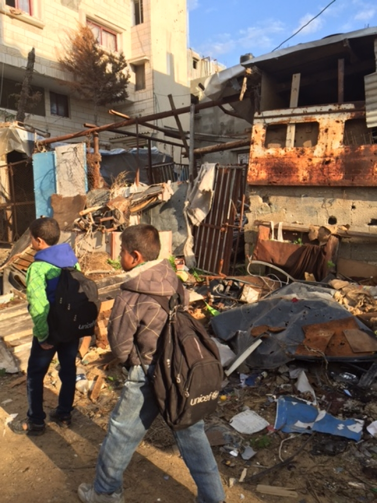 Children walking through the rubble of Gaza