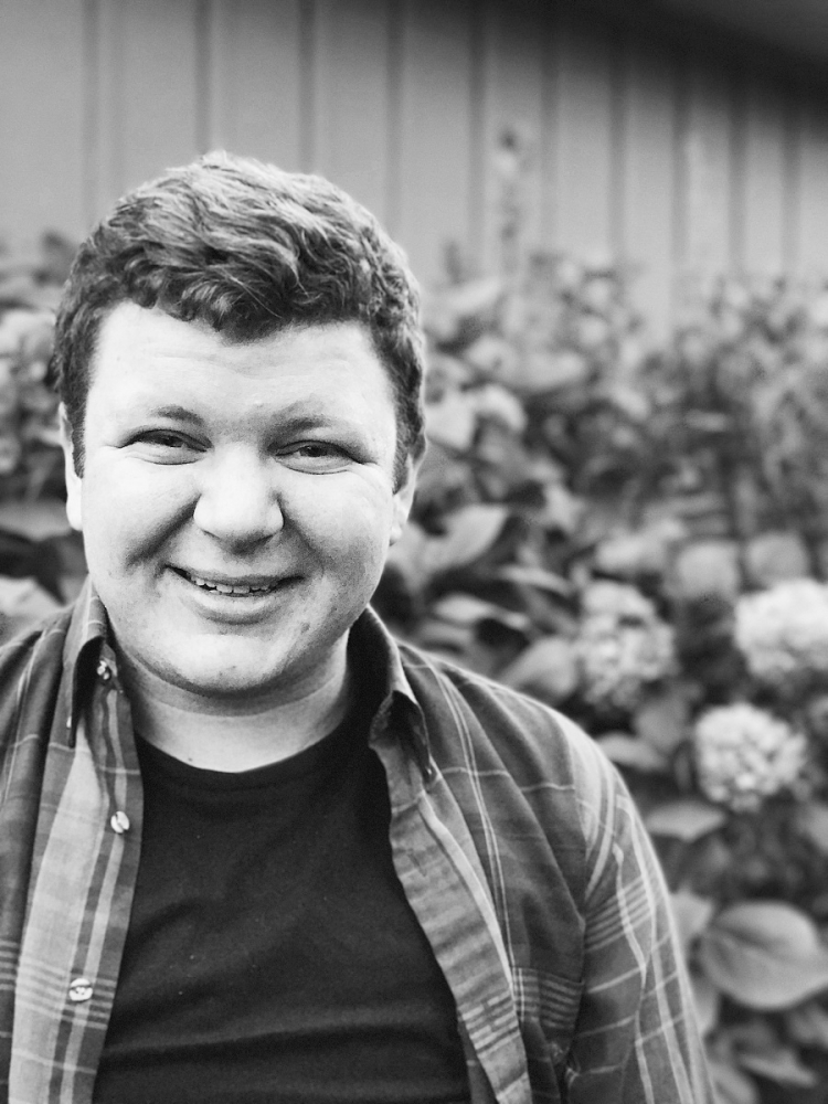 Elijah, smiling, in Black and White filter with flowers in the background
