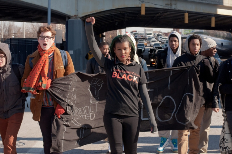 Youth raising fist while marching with group in Black Lives Matter protest