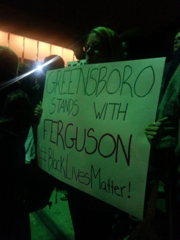 """Woman holding """"Greensboro stands with Ferguson"""" sign"""