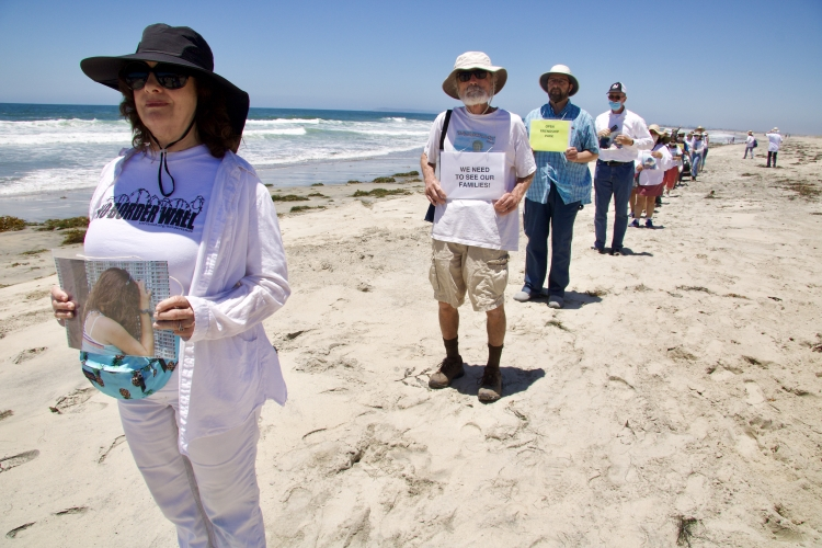 Community members take part in an action at the beach of Friendship Park, walking in silence while holding photos of family reunions at Friendship Park. Photo: Pedro Rios/AFSC