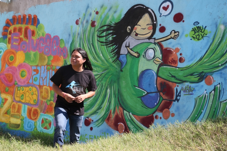 Saulo Hernandez in front of a mural in Guatemala