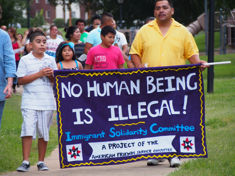 "Man and children holding ""no one is illegal"" banner"