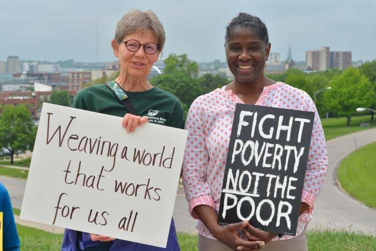 "People hold signs saying ""Weaving a world that works for us all"" and ""Fight poverty not the poor"""
