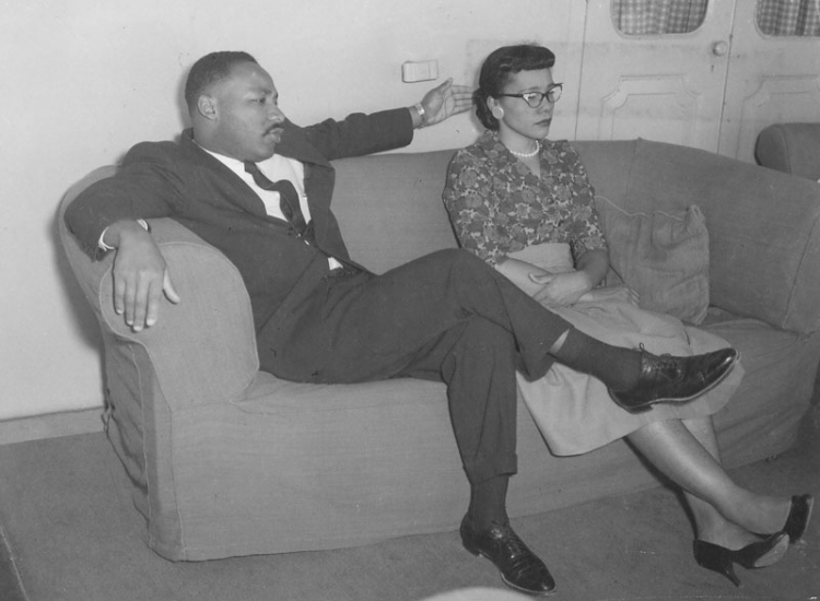 Martin Luther King, Jr. and Coretta Scott King sit on a couch, in conversation.