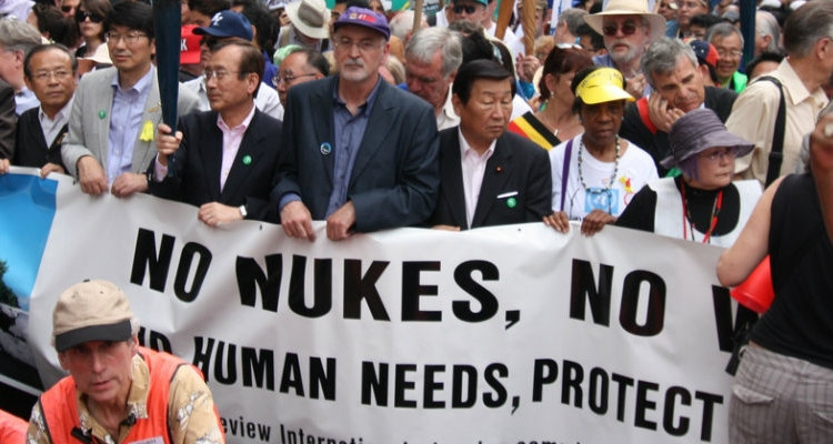 """Protesters march is a banner that reads """"no nukes, no war"""""""