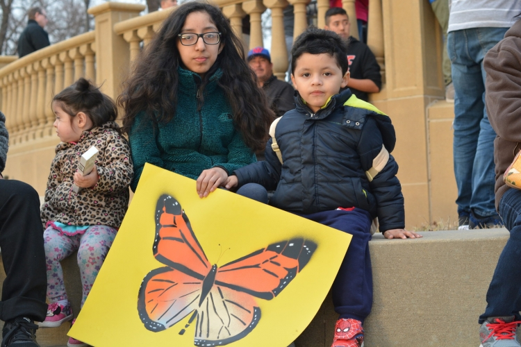People with butterfly poster in front of state capitol
