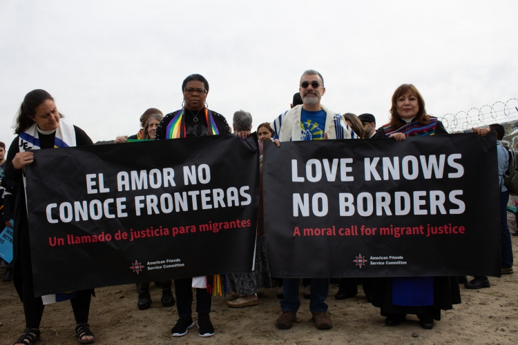 People with banners at the Love Knows No Borders action in San Diego