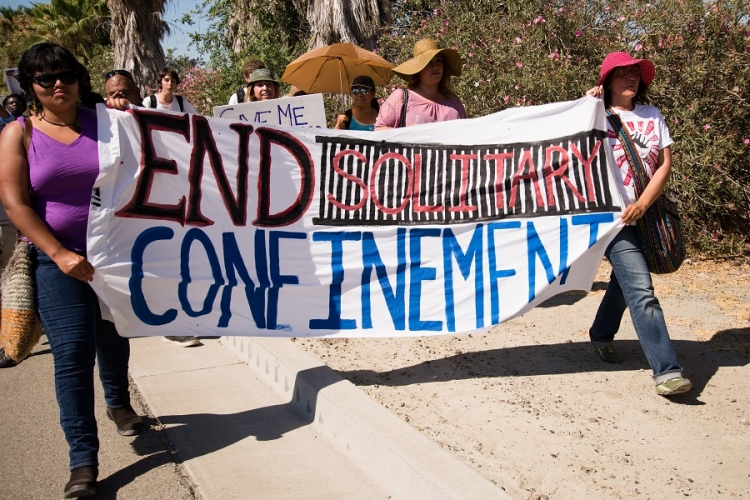 "People with banner reading ""End Solitary Confinement"" at a rally to support Corcoran Prison hunger strikers, California, 2013."