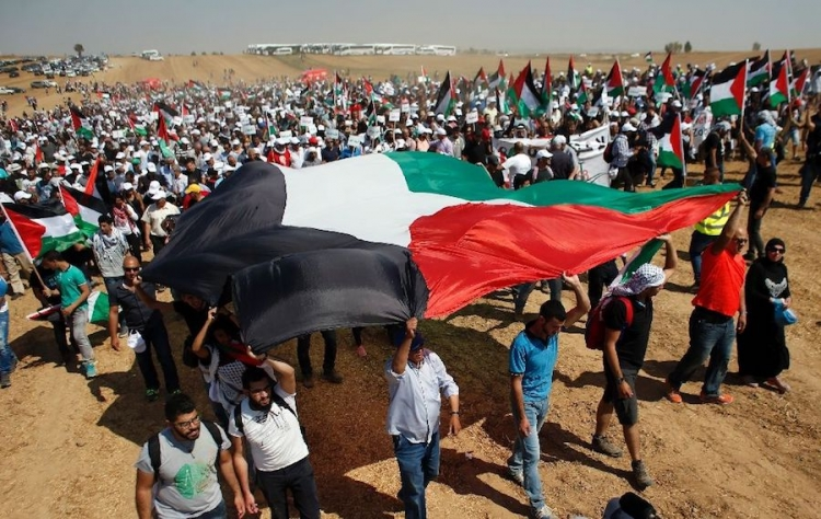 Palestinians march for return carrying large Palestinian flag