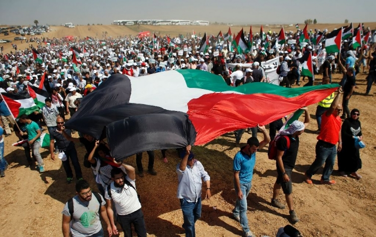 Palestinians marching for right of return with giant Palestinian flag
