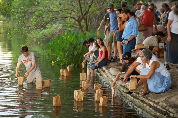 People light and float luminaries on a river