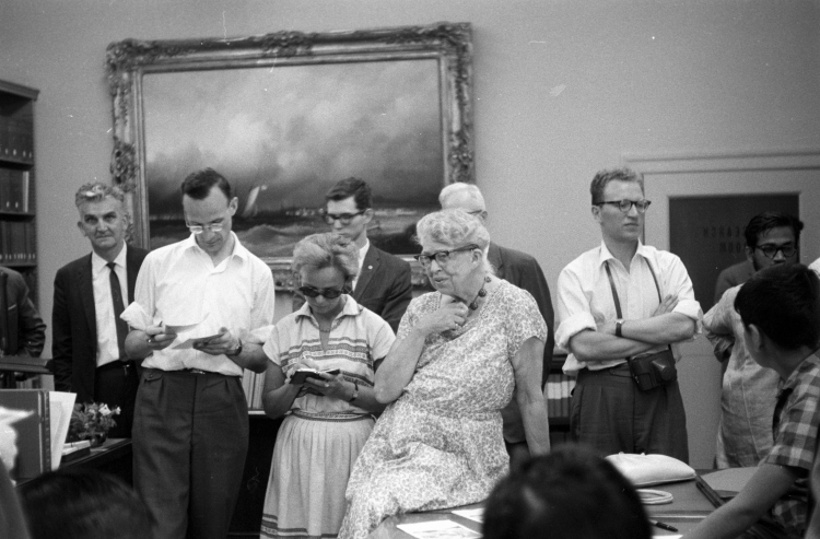 Woman sits on a desk, surrounded by men and women
