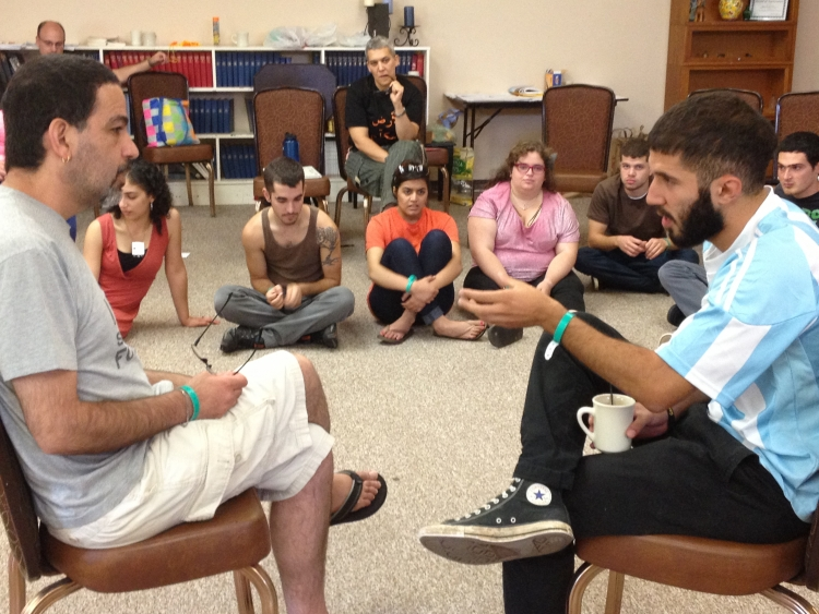 A trainer and participant talk during a fish bowl exercise at the 2013 SLT