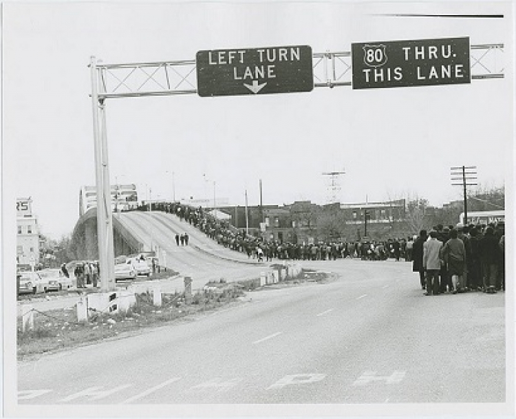Black and white photo of Selma march crossing the Edmund Pettus bridge